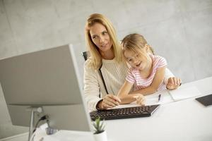 Mother trying to get work done with daughter photo