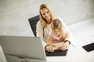 Mother working with daughter in lap photo