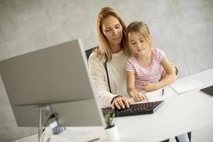 Mother typing with daughter on her lap photo