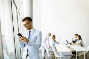 Businessman on phone with team in the background photo