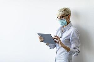 Masked mature businesswoman using a tablet with copy space photo