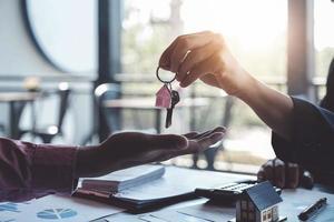 Los agentes inmobiliarios acuerdan comprar una vivienda y entregar las llaves a los clientes en las oficinas de su agencia. acuerdo de concepto foto