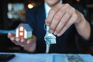 Bank officer give key house to customer after making a home purchase contract photo