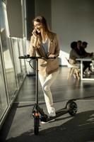Woman on phone with scooter in office photo