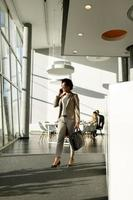 Businesswoman walking and talking on phone photo