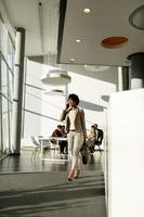 Businesswoman walking and talking on phone in an airport photo
