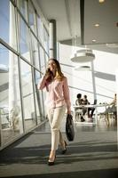 Businesswoman on cell phone walking in the office photo