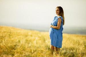 Pregnant woman in blue dress in field photo