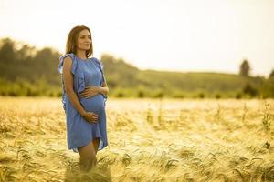 Pregnant woman in blue dress in golden sunlight photo