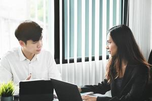 Two young business executives are discussing to change their business concept to increase profits and the strength of their business photo