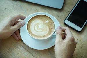 Una mano de hombre sosteniendo una taza de café en un escritorio de madera con teléfono inteligente y computadora portátil en la oficina foto