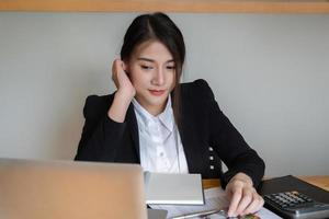Businesswoman or accountants are working at the office to verify the accuracy of the account using a calculator and laptop computer photo
