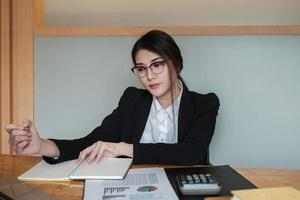 Businesswomen wearing glasses are working at the office to verify the accuracy of the account using a calculator photo