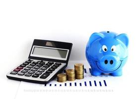 Calculator money coin stack and blue piggy bank for loans concept photo