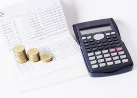 Money coins stack and calculator and book bank loan money concept photo