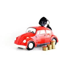 Car key into car bank and coins stack on white background for loans concept photo