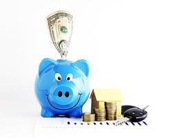 Piggy bank with dollar and coins stack and home paper with car keys for loan money concept photo