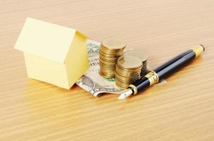 Home loans concept with house paper and fountain pen with dollar money coins stack on wooden desk background photo