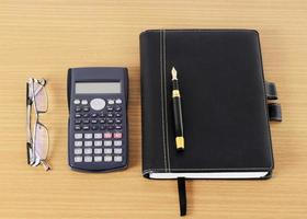 Fountain pen and business book with calculator and eyeglasses on wooden desk for office work place concept photo