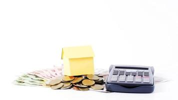 Home paper and calculator with money coins stack for loans concept photo