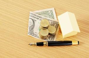 Fountain pen and dollar money with coins stack and home paper for loans concept photo