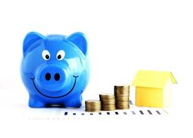 Blue piggy bank and coins stack and house paper for home loans concept photo