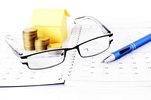 Loan concept with eyeglasses and pen and coins stack and paper house on book pages photo