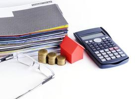 Loans concept with close up of house paper and coins stack with calculator and eyeglasses for bill payment concept photo