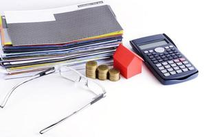 Loans concept with bill payment and calculator and coins and house paper and eyeglasses photo