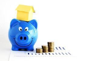 Piggy bank and house paper and coins stack for home loans concept photo