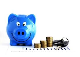 Blue piggy bank and money coins stack and car key for loans concept photo