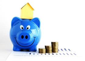 House paper on piggy bank and coins for loans concept photo