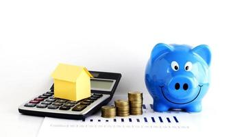 House paper on calculator with coins and piggy bank for home loans concept photo