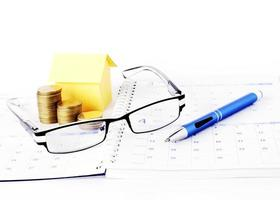 Loans concept with eyeglasses and blue pen with money coins and yellow paper house on calendar book page photo