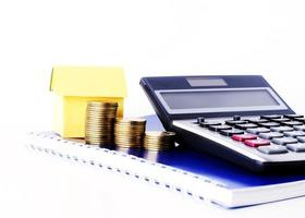 Money coins stack and paper house and calculator on blue diary book for loans concept photo