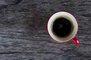 Tazas de café negro rojo sobre fondo de mesa de madera, vista superior foto