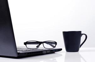 Black coffee cup and eyeglasses put on laptop on white background photo