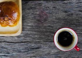 Taza de café negro y bollo rojo sobre fondo de placa de madera foto