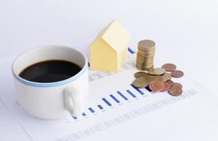 Money coins stack and house paper with coffee cup on chart for home loans money concept photo