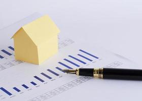 Close up of fountain pen and house paper on chart for loan money concept photo