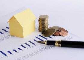House paper and coins stack and fountain pen for home loans concept photo