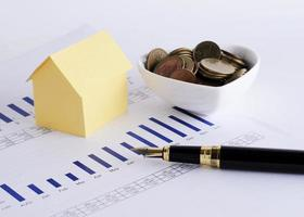 Fountain pen and house paper and coins in cup for home loans concept photo