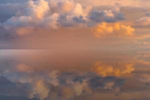Magical pale pink sky with fluffy colorful clouds photo