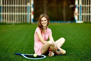 Girl sitting on the lawn of a tennis field with a tennis racket photo