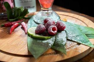 Fresh raspberries on green leaves with peppercorns sprinkled with powdered sugar photo