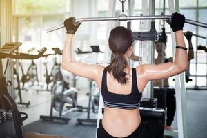 Woman using work out machine at the gym photo