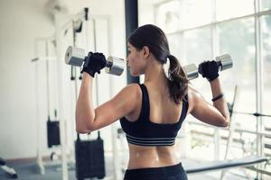 Woman lifting weight in the gym photo