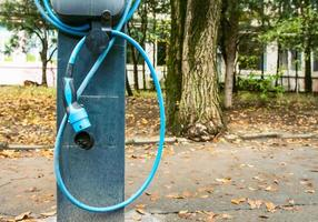 Close up of electric car charging station with loose hose and trees in the background photo