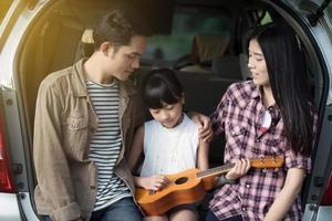 Family playing ukulele together on camping trip photo