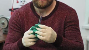 un maestro masculino afila las tijeras en un taller y comprueba la nitidez video